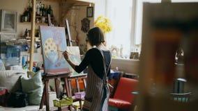 Bakre sikt av den unga målareflickan i bild för förklädemålningstilleben på kanfas i konst-grupp lager videofilmer
