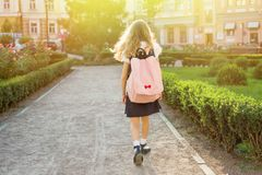Bakre sikt av den unga skolflickan i likformig med ryggsäcken som går till Royaltyfria Bilder
