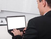 Bakre sikt av den upptagna användande bärbara datorn för affärsman på kontorsskrivbordet Arkivbild