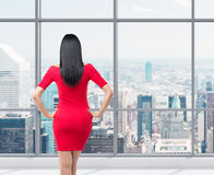 Bakre sikt av den ursnygga brunetten i röd klänning Royaltyfri Fotografi