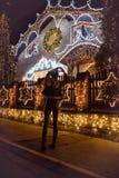 Bakre sikt av det kvinnliga hållande tomteblosset mot julljus de royaltyfri fotografi