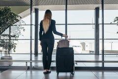 Bakre sikt av det slanka unga kvinnliga handelsresandeanseendet i hållande tunga resväskor för flygplatsterminal som ser till och Royaltyfri Foto