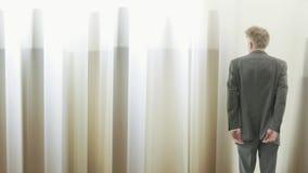 Bakre sikt av en affärsman som ser till och med gardiner stock video
