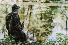 Bakre sikt av en angenäm fiskare som tycker om hans hobby fotografering för bildbyråer