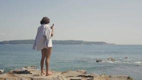 Bakre sikt av en danandebild för ung kvinna på kamera för celltelefon, medan att tycka om hennes semester semestrar på kusten lager videofilmer