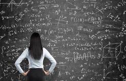 Bakre sikt av en fundersam kvinna som försöker att lösa matematikproblem Arkivbild