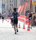 Bakre sikt av en grupp av löpare i en kullerstengränd Royaltyfria Bilder