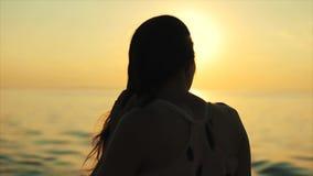 Bakre sikt av en härlig flicka som håller ögonen på havssolnedgången långsam rörelse Närbild lager videofilmer