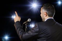 Bakre sikt av en högtalare som talar på mikrofonen Arkivfoton
