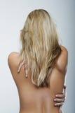 Bakre sikt av en kal blond kvinna mot grå färger royaltyfri bild
