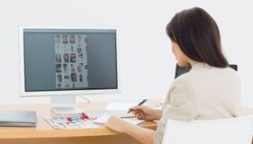 Bakre sikt av en konstnär på skrivbordet med datoren i regeringsställning Fotografering för Bildbyråer