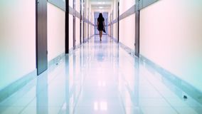 Bakre sikt av en kvinna i en svart klänning som promenerar korridoren av hotellet Hon rymmer skor i hennes hand stock video