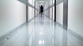 Bakre sikt av en kvinna i en svart klänning som promenerar korridoren av hotellet Hon rymmer skor i hennes hand lager videofilmer