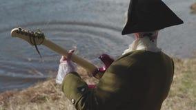 Bakre sikt av en man i gammalmodig dräkt och den vita peruken med den reste upp hatten som spelar gitarren på en flodkust materie stock video