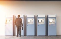 Bakre sikt av en man nära fem ATM-maskiner Arkivbilder