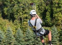 Bakre sikt av en man på en zipline som går ner en dal i skog arkivbilder