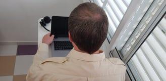 Bakre sikt av en man som bär den officiella krageskjortan som sitter nära fönster royaltyfri fotografi
