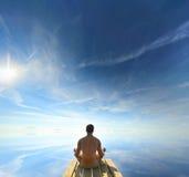 Bakre sikt av en man som mediterar i en Lotus Yoga Position på flodstranden Arkivfoto