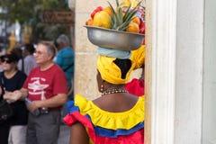 Bakre sikt av en palenquera som säljer frukter i Cartagena royaltyfria foton