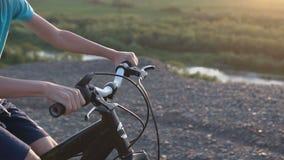 Bakre sikt av en pojke som rider en svart cykel i ett bergsområde Cykla för barn Ung pojke som rider en cykel på berget arkivfilmer
