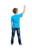 Bakre sikt av en skolapojke över vit bakgrund som uppåt pekar Arkivfoton