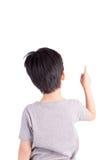 Bakre sikt av en skolapojke över vit bakgrund som uppåt pekar Arkivbilder