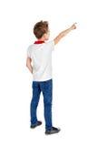 Bakre sikt av en skolapojke över vit bakgrund som uppåt pekar Royaltyfri Foto