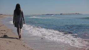 Bakre sikt av en slank sexig härlig flicka som barfota går på sanden längs kusten arkivfilmer