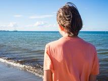 Bakre sikt av en tonåringpojke på stranden fotografering för bildbyråer