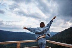Bakre sikt av en trevlig kvinna som tycker om bergsikt royaltyfri foto
