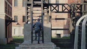 Bakre sikt av en tysk soldat med ett gevär som upp går trappan av en watchtower WWII-reenactment stock video
