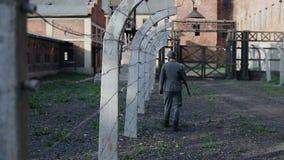 Bakre sikt av en tysk soldat som promenerar ett taggtrådstaket som bevakar en koncentrationsläger Reenactment av WWII stock video