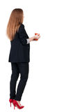 Bakre sikt av en ung affärskvinna som dricker kaffe eller te medan Arkivbilder