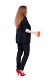 Bakre sikt av en ung affärskvinna som dricker kaffe eller te medan Royaltyfria Foton
