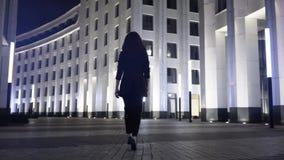 Bakre sikt av en ung affärskvinna som går i en nattstadsgata arkivfilmer