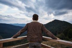 Bakre sikt av ett manligt anseende på balkongen arkivfoton