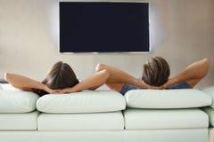 Bakre sikt av ett par som hemma kopplar av på en soffa och en hållande ögonen på TV arkivfoton