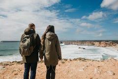 Bakre sikt av ett ungt par av turister eller handelsresande royaltyfri foto