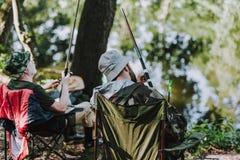 Bakre sikt av förtjusta män som tycker om att fiska på flodbanken royaltyfri fotografi