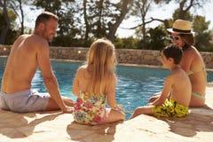 Bakre sikt av familjen på semester som kopplar av vid den utomhus- pölen arkivfoto