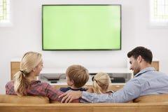 Bakre sikt av familjsammanträde på Sofa In Lounge Watching Televisio fotografering för bildbyråer