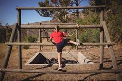 Bakre sikt av flickan som klättrar utomhus- utrustning under hinderkurs arkivbild