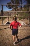 Bakre sikt av flickan som ser utomhus- utrustning under hinderkurs royaltyfri foto