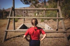 Bakre sikt av flickan som ser utomhus- utrustning under hinderkurs fotografering för bildbyråer