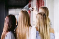 Bakre sikt av fyra flickor som gör selfie Arkivbild