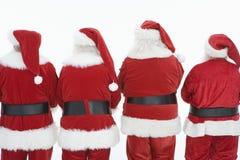 Bakre sikt av fyra män iklädda Santa Claus Outfits Royaltyfri Bild