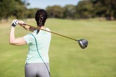 Bakre sikt av golfarekvinnan som tar skottet Royaltyfri Bild
