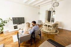 Bakre sikt av hållande ögonen på television för par i vardagsrum Royaltyfri Bild