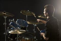Bakre sikt av handelsresanden Playing Drum Kit In Studio arkivbilder