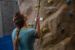 Bakre sikt av idrottsman nenanseendet, genom att klättra väggen med repet i konditionstudio Royaltyfria Foton